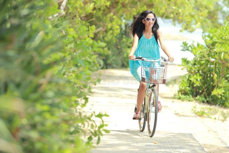 Mulher que tem a bicicleta da equitação do divertimento na praia imagem de stock