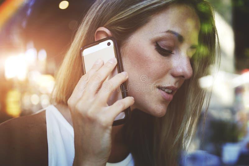 mulher que tem a conversação telefônica da pilha na cafetaria foto de stock royalty free