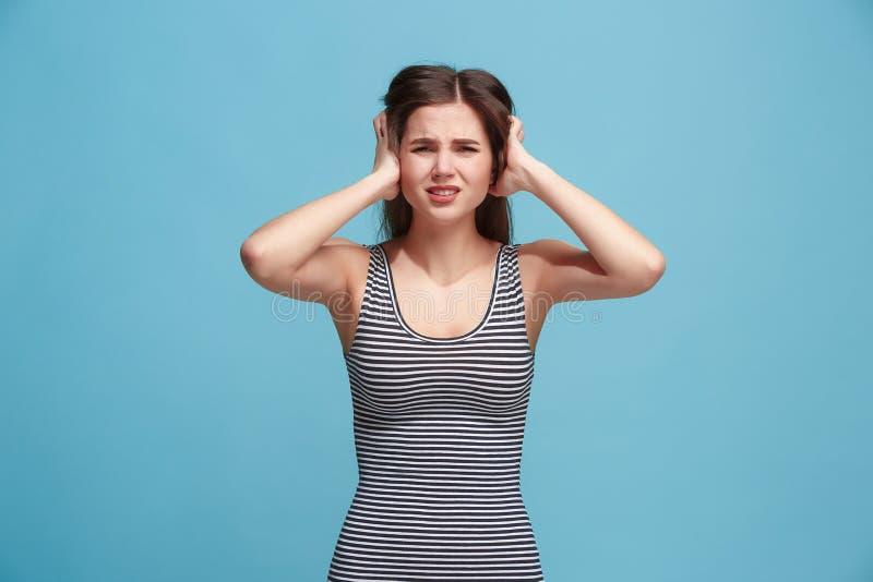 Mulher que tem a dor de cabeça Isolado sobre o fundo azul fotos de stock