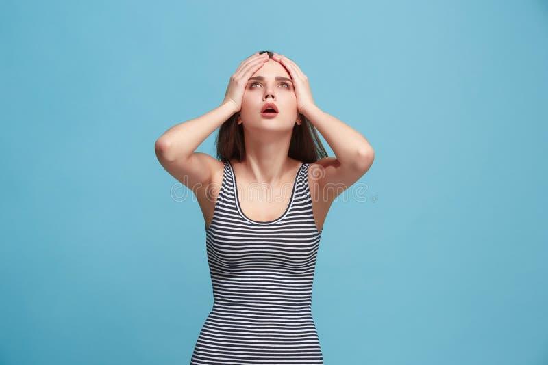 Mulher que tem a dor de cabeça Isolado sobre o fundo azul imagem de stock royalty free
