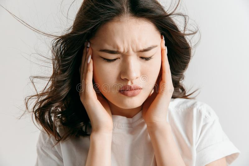 Mulher que tem a dor de cabeça Isolado sobre o fundo cinzento imagem de stock royalty free