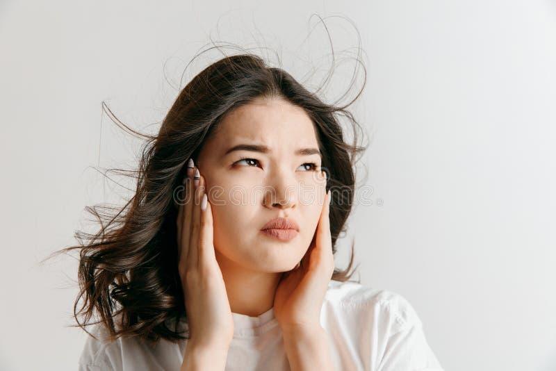 Mulher que tem a dor de cabeça Isolado sobre o fundo cinzento foto de stock