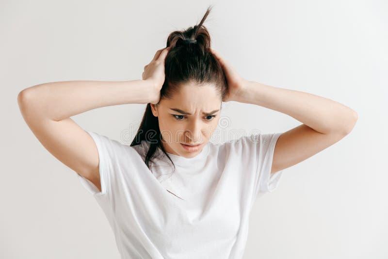 Mulher que tem a dor de cabeça Isolado sobre o fundo cinzento imagens de stock