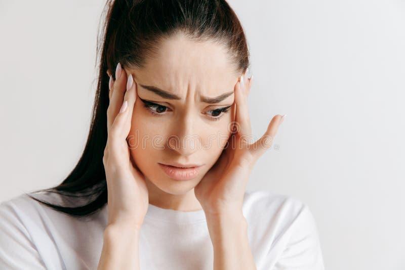 Mulher que tem a dor de cabeça Sobre o fundo cinzento imagens de stock