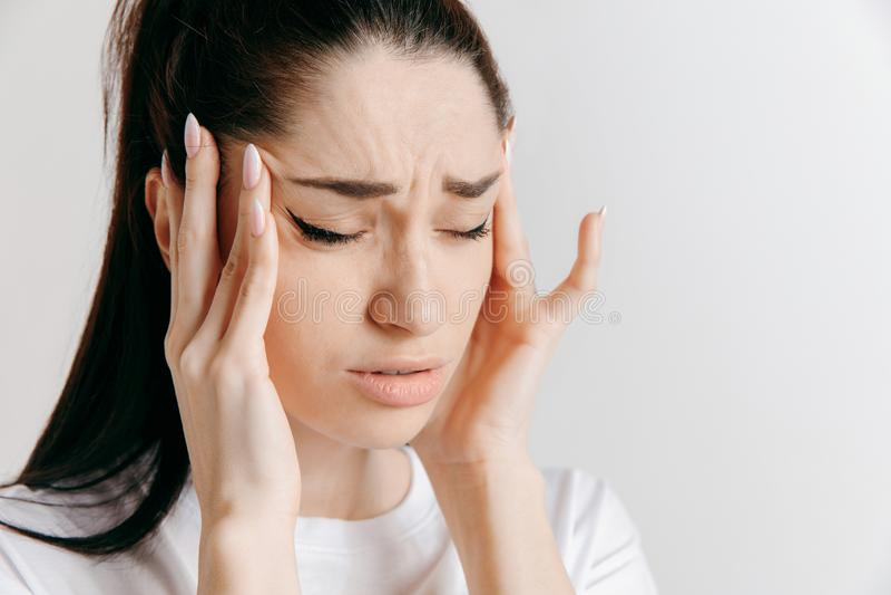 Mulher que tem a dor de cabeça Sobre o fundo cinzento foto de stock