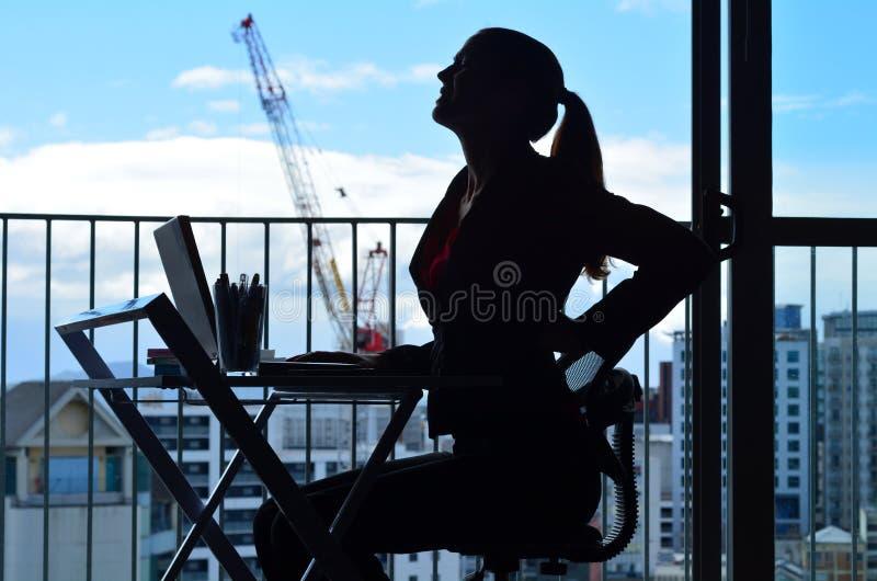 Mulher que tem a dor nas costas ao trabalhar na mesa de escritório imagem de stock