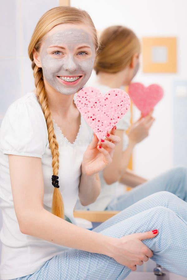 Mulher que tem a máscara protetora cinzenta que guarda a esponja do coração imagens de stock royalty free