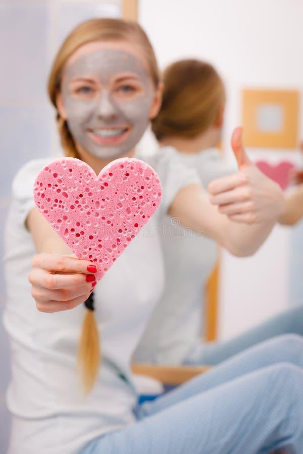 Mulher que tem a máscara protetora cinzenta que guarda a esponja do coração fotografia de stock