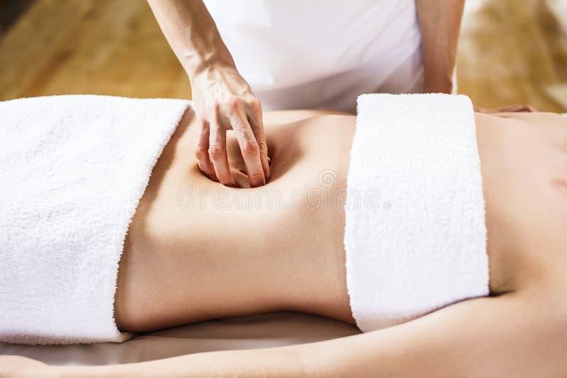 Mulher que tem a massagem do abdômen foto de stock