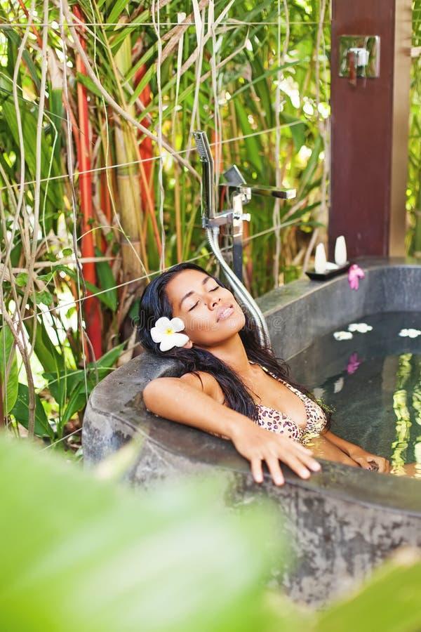 Mulher que tem o banho em um salão de beleza luxuoso dos termas foto de stock