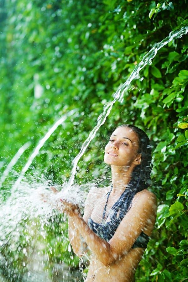 Mulher que tem o chuveiro sob a cachoeira tropical fotos de stock royalty free
