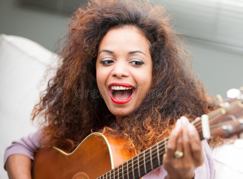 Mulher que tem o divertimento com sua guitarra fotografia de stock royalty free