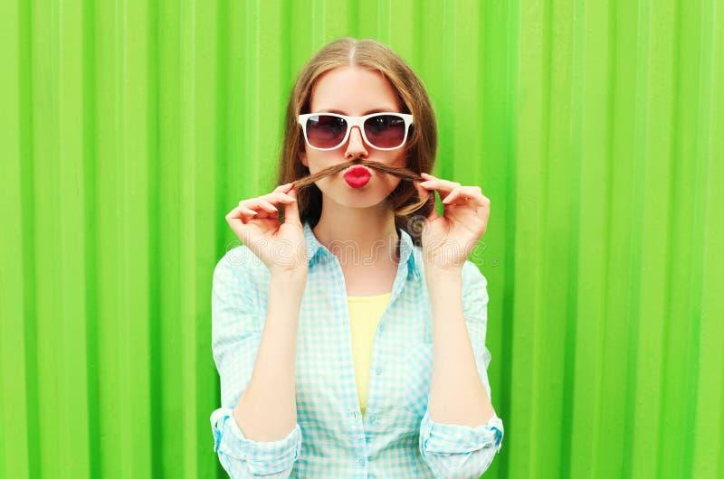 A mulher que tem o divertimento mostra o cabelo do bigode sobre o verde foto de stock royalty free