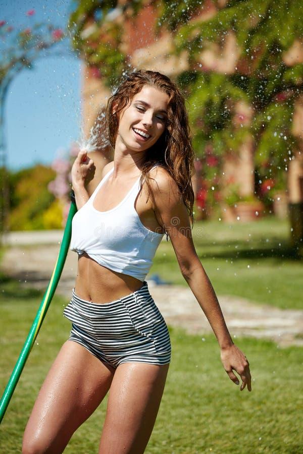 mulher que tem o divertimento no jardim do verão imagem de stock