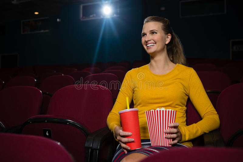 Mulher que tem a pipoca e as bebidas ao olhar o filme no teatro fotografia de stock