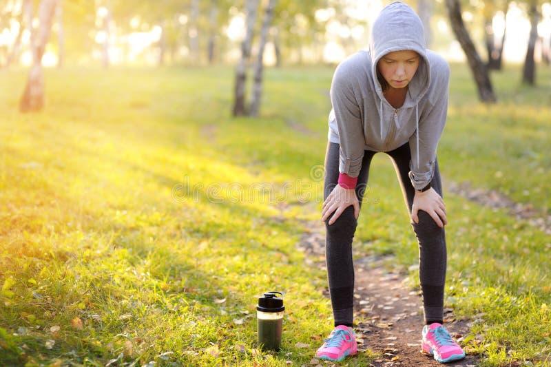 Mulher que tem um resto após o exercício duro em um campo de esportes imagem de stock