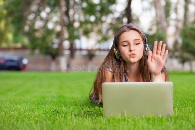 Mulher que tem uma chamada video com um portátil e os fones de ouvido que fundem um beijo virtual que cumprimenta um amigo fotos de stock