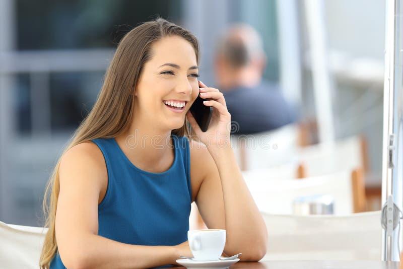 Mulher que tem uma conversa telefônica em uma barra imagens de stock