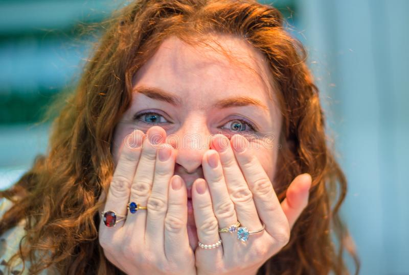 Mulher que tenta anéis caros na loja de joia imagens de stock