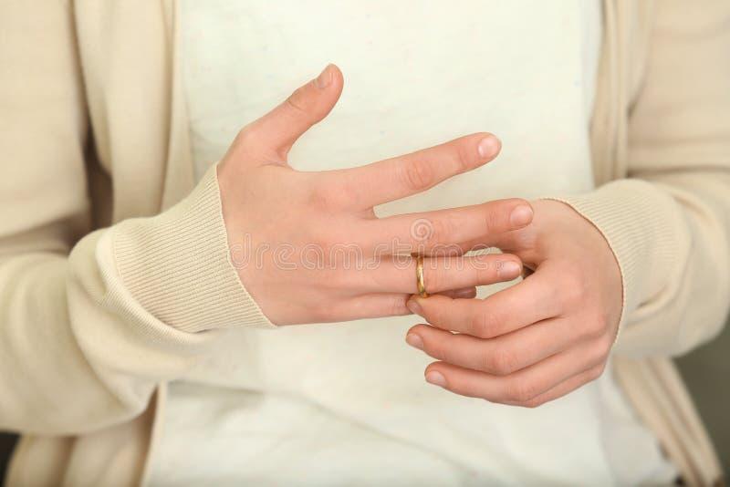 Mulher que tenta ao anel deslizante fora de seu dedo, close up Conceito do div?rcio fotografia de stock