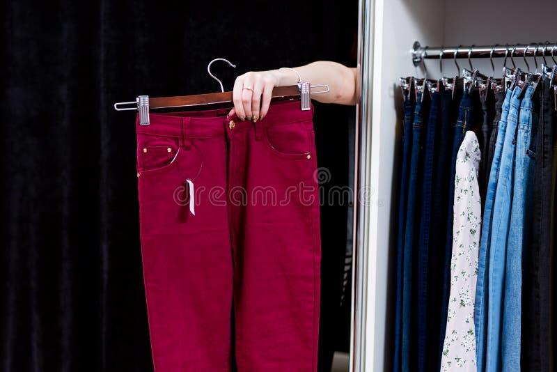 Mulher que tenta em calças em uma loja de roupa que alcança para fora a mão de uma sala apropriada que guarda a calças foto de stock royalty free