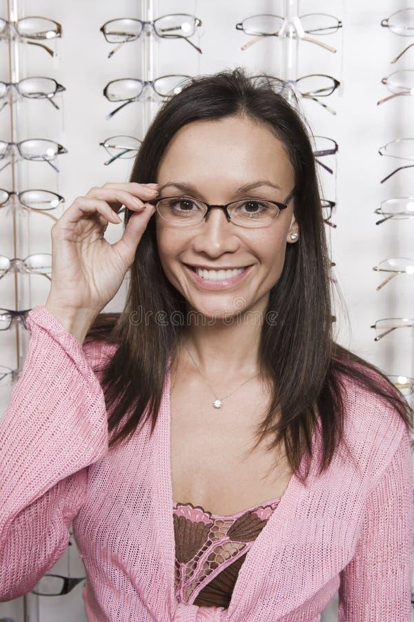 Mulher que tenta em monóculos na loja foto de stock