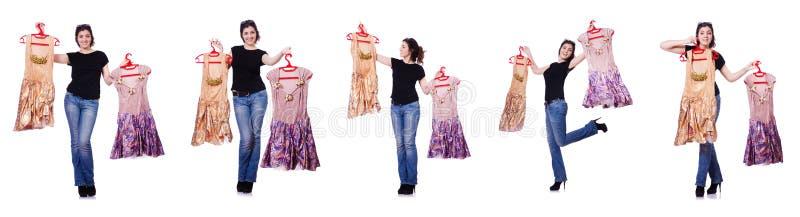 A mulher que tenta escolher o vestido no branco fotografia de stock royalty free