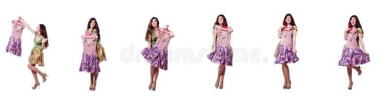 A mulher que tenta escolher o vestido no branco foto de stock