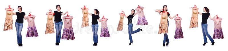 A mulher que tenta escolher o vestido no branco foto de stock royalty free