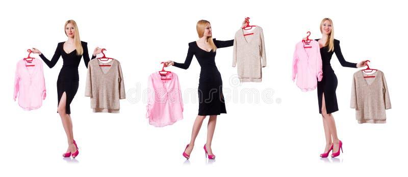 A mulher que tenta escolher o vestido no branco imagens de stock