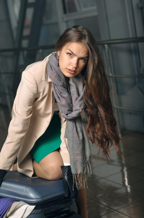 Mulher que tenta fechar a mala de viagem fotografia de stock