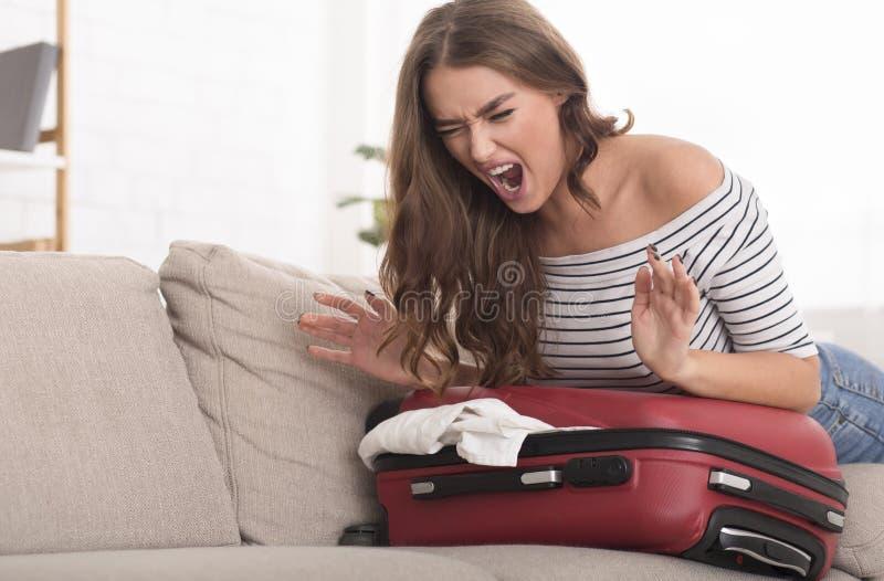 Mulher que tenta fechar a mala de viagem e ficar irritado fotografia de stock