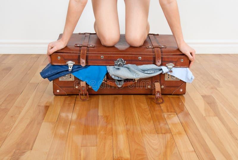 Mulher que tenta fechar a mala de viagem enchida em demasia fotografia de stock