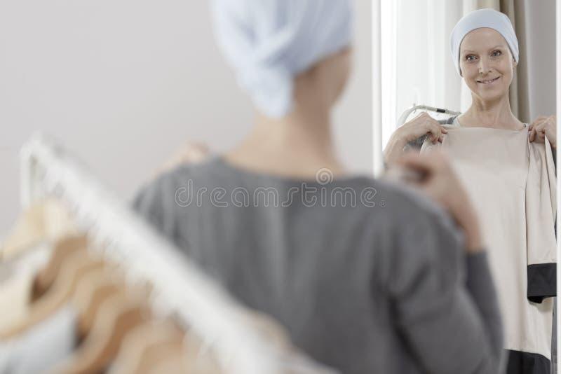 Mulher que tenta na roupa nova fotografia de stock