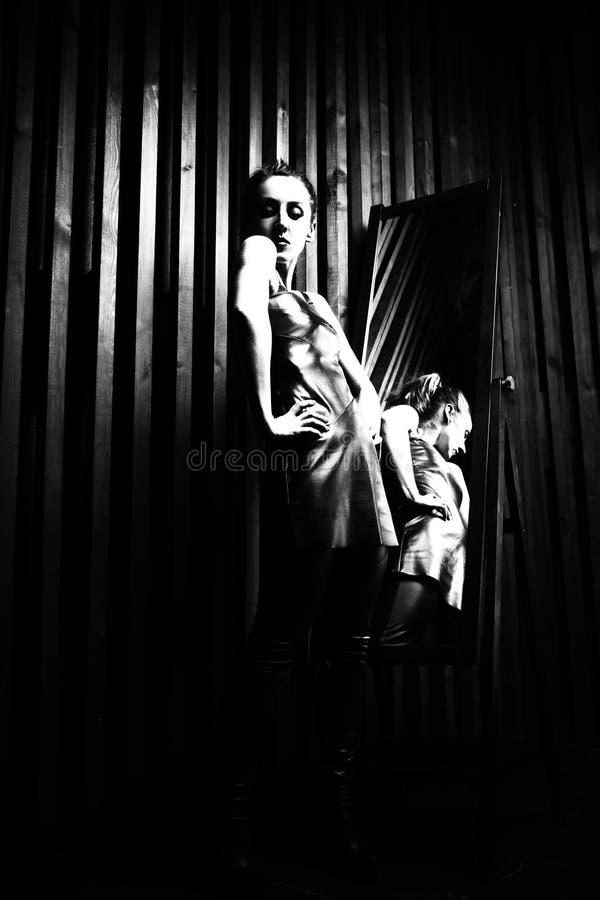 Mulher que tenta no vestido na frente do espelho foto de stock