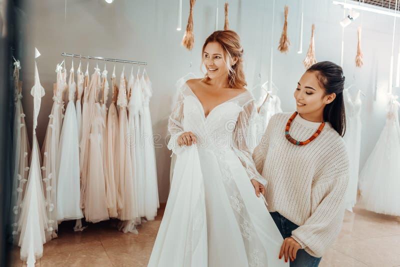 Mulher que tenta um vestido de casamento na frente de um espelho imagens de stock