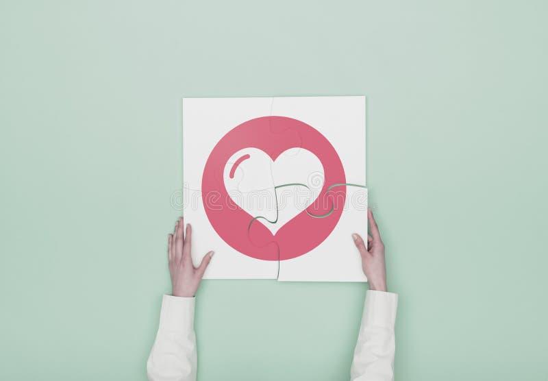 Mulher que termina um enigma com ícone do coração fotografia de stock royalty free