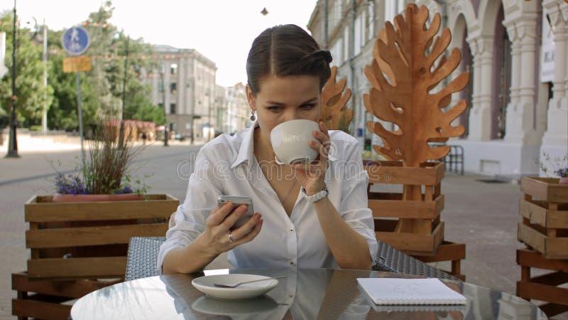 Mulher que texting Menina bonita alegre de sorriso feliz nova do close up que olha a leitura móvel do telefone celular que envia  fotografia de stock
