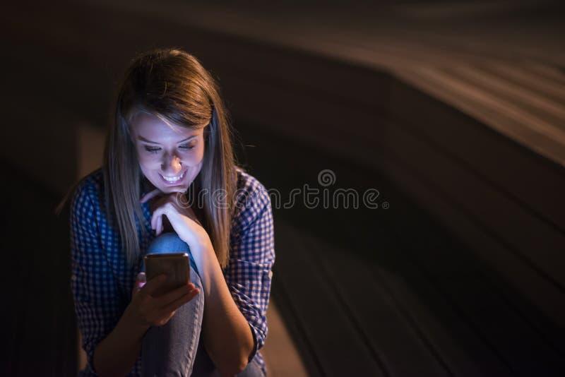 Mulher que texting Mulher bonita alegre de sorriso feliz nova do close up que olha a leitura móvel do telefone celular que envia  fotos de stock