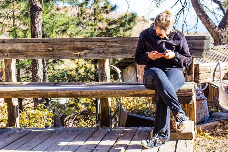 Mulher que Texting no telefone celular no banco de madeira rústico fotografia de stock