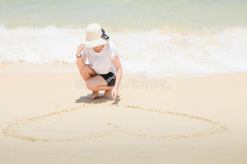 Mulher que tira um coração na areia na praia imagem de stock
