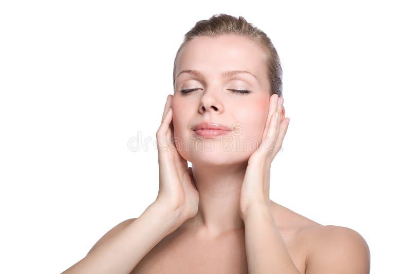 Mulher que toca com sua mão na pele saudável imagem de stock