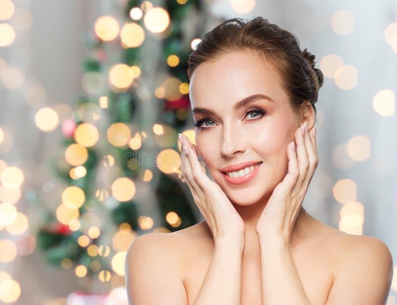 Mulher que toca em sua cara sobre luzes de Natal imagens de stock