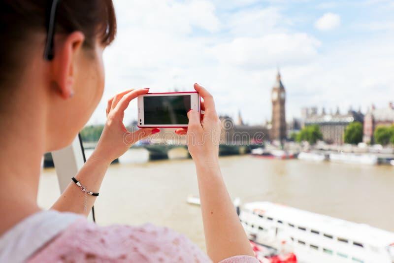 Mulher que toma as imagens de Big Ben, Londres Reino Unido com o smartphone, móvel imagens de stock royalty free