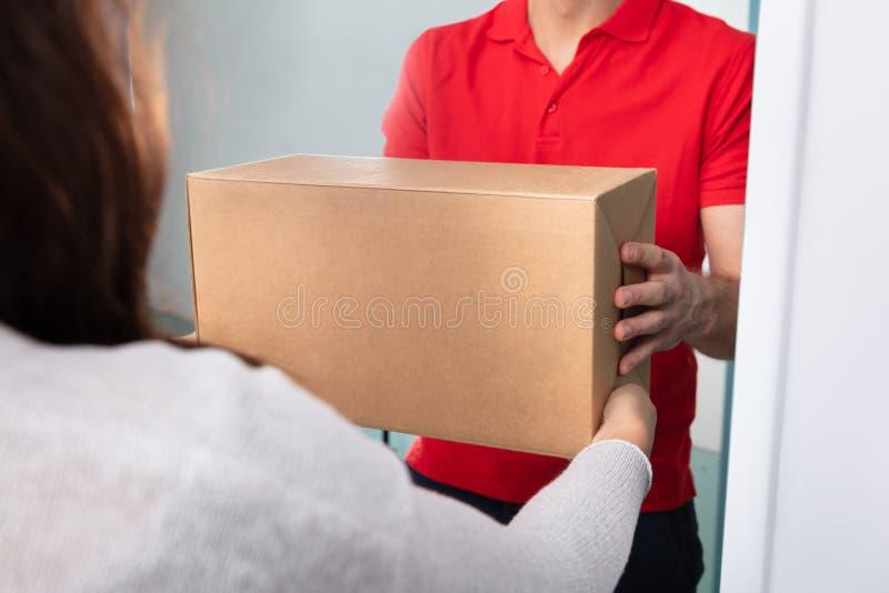 Mulher que toma a caixa do homem de entrega imagem de stock royalty free