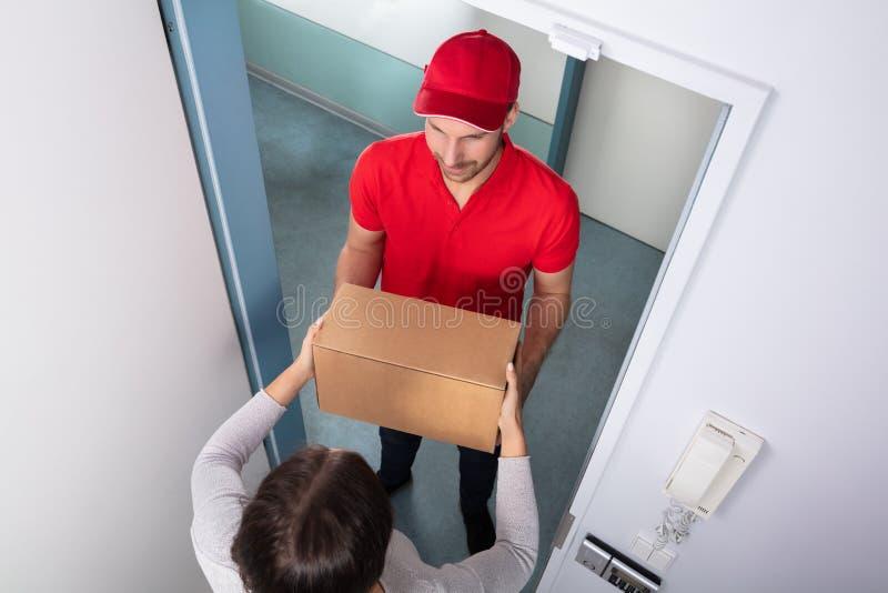 Mulher que toma a caixa do homem de entrega fotos de stock
