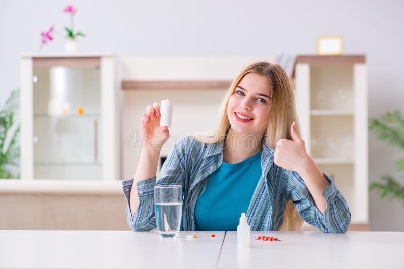 A mulher que toma comprimidos para lidar com a dor imagem de stock