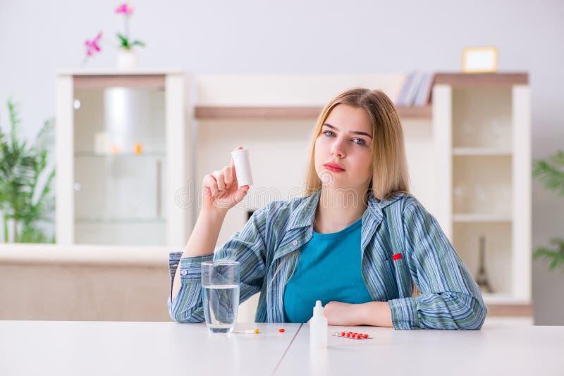 A mulher que toma comprimidos para lidar com a dor foto de stock