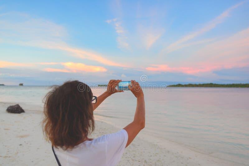Mulher que toma a foto com o smartphone do céu romântico no por do sol na praia da areia, vista traseira, pessoa real que viaja e fotos de stock royalty free