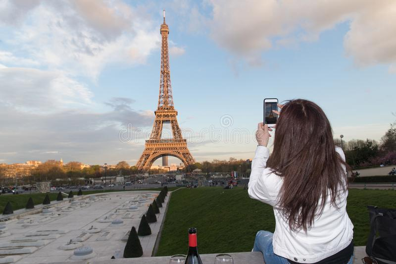 Mulher que toma a foto da torre Eiffel em Paris, França com cellpho imagem de stock royalty free